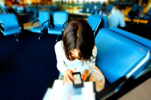 woman-looks-at-phone-at-airport_o